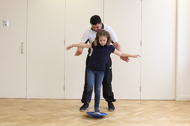 Child balancing on wobble board, therapist behind offering support