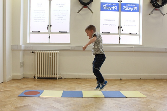 Child jumping between mats during an assessment