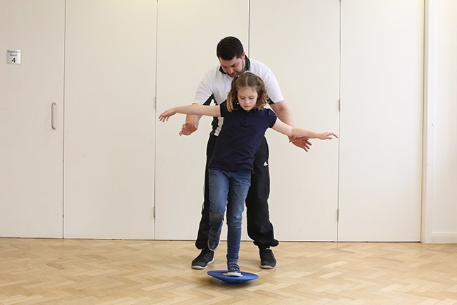 Child balancing on wobble board on one leg, Therapist behind for support