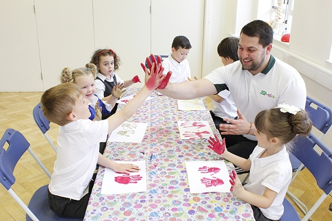Therapist high fiving a child with painted hands, other children watching and pressing hands onto paper