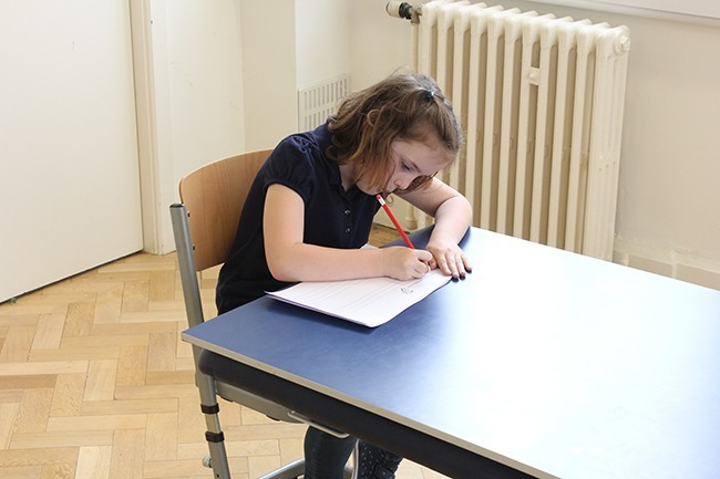 Child writing on a sloped writing board, leaning forward