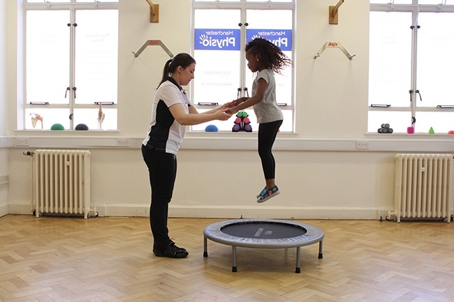 Therapist helping child bounce on a trampoline