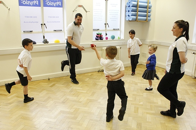 Children throwing beanbag, stood on one leg in a group