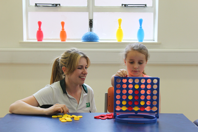 Therapist playing connect four with a young girl