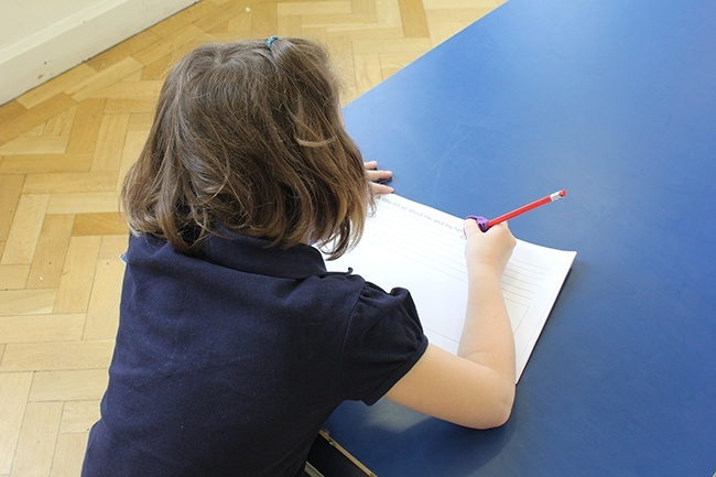Child writing, over the shoulder angle