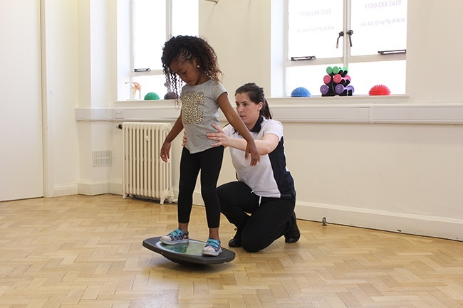 Child balancing on wobble board, therapist offering support