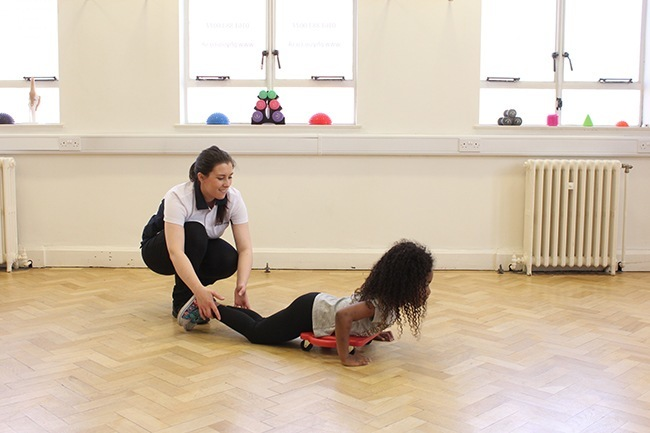 Child lying on scooter board being pulled by therapist