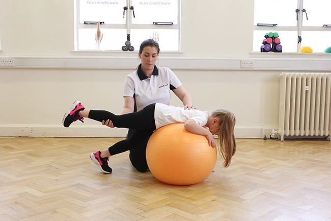 Child lying on therapy ball, therapist providing support