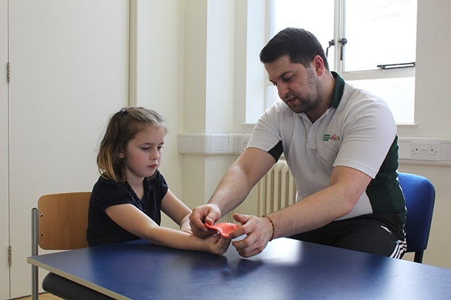 Therapist helping child open her hand against putty