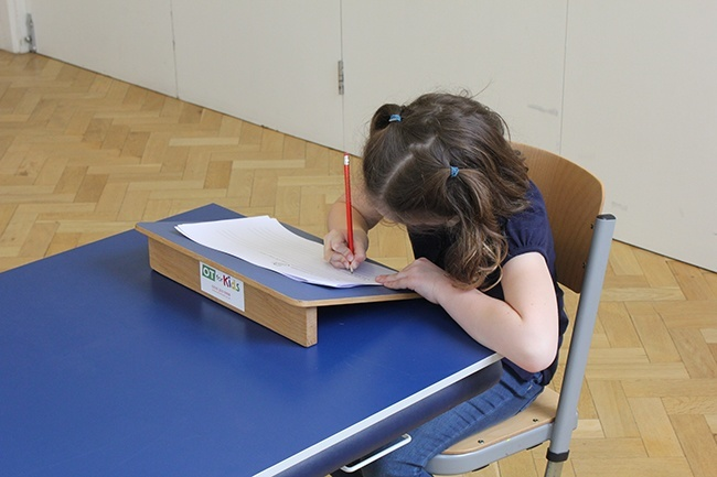 Child writing, using a sloped writing board to help