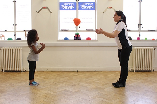 Therapist throwing a ball to child