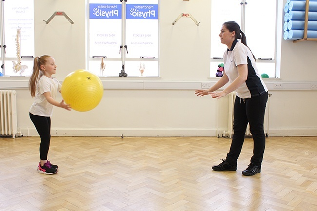 Child and Therapist throwing a large ball to each other